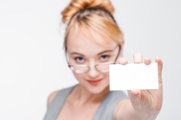 コピースペースと白い空のカードを示す眼鏡とベストの素敵な若い女の子。灰色の壁にぼやけた肖像画、白紙に焦点を当て、顔をクローズアップ
