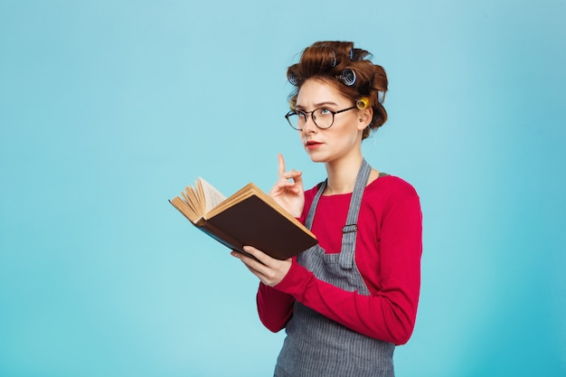 Nice young girl with curlers and glasses dived into reading