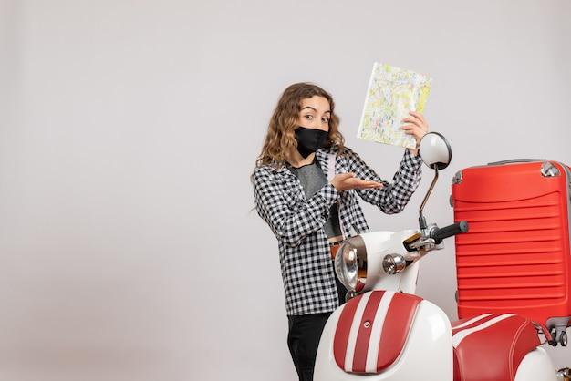 Bella ragazza con maschera che tiene la mappa in piedi vicino al motorino con la valigia rossa red