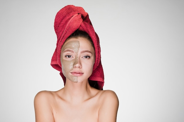 Nice young girl with a red towel mn agolove applied a clay useful mask to half the face
