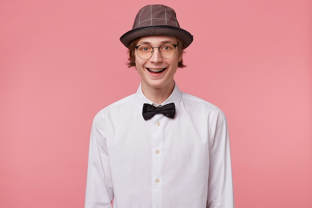Nice young guy in white shirt, hat and black bowtie wears glasses happily widely smiling showing orthodontic brackets, isolated on pink background