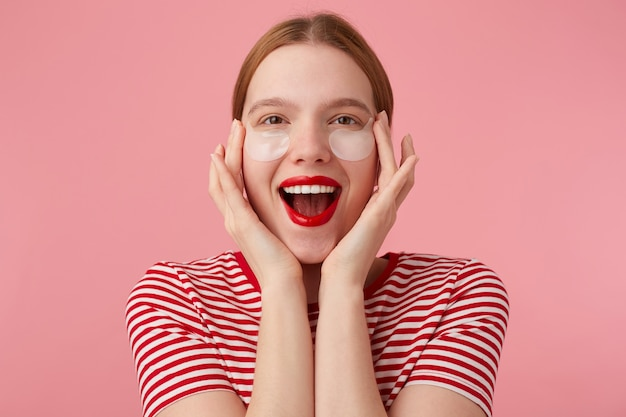 Bella giovane signora dai capelli rossi felice in una maglietta a strisce rosse, con le labbra rosse, si tocca il viso con le dita, molto soddisfatta delle nuove toppe. stand.