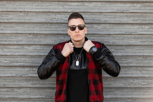 Nice young hipster man in a fashionable plaid jacket in a black t-shirt with stylish sunglasses is posing next to a wooden vintage wall. handsome modern guy fashion model