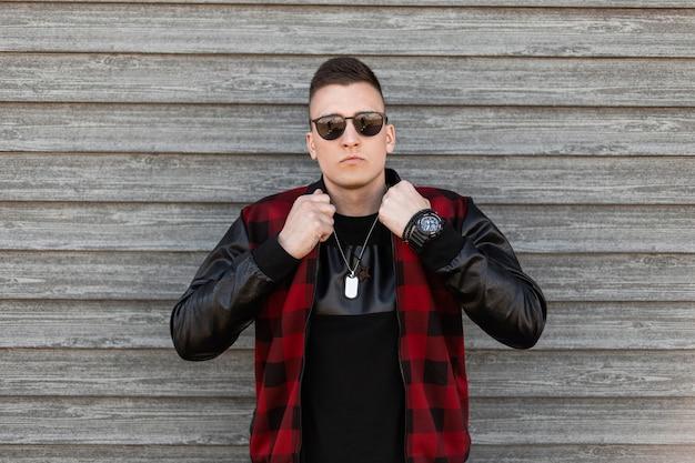 세련 된 선글라스와 검은 티셔츠에 세련 된 격자 무늬 재킷에 좋은 젊은 hipster 남자는 나무 빈티지 벽 옆에 포즈입니다. 잘 생긴 현대 남자 패션 모델