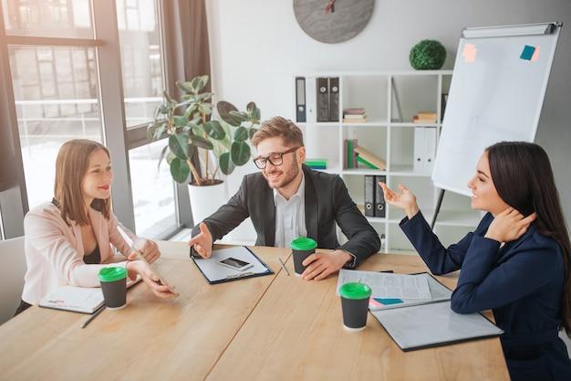 素敵な若い男性と女性が会議室のテーブルに一緒に座る