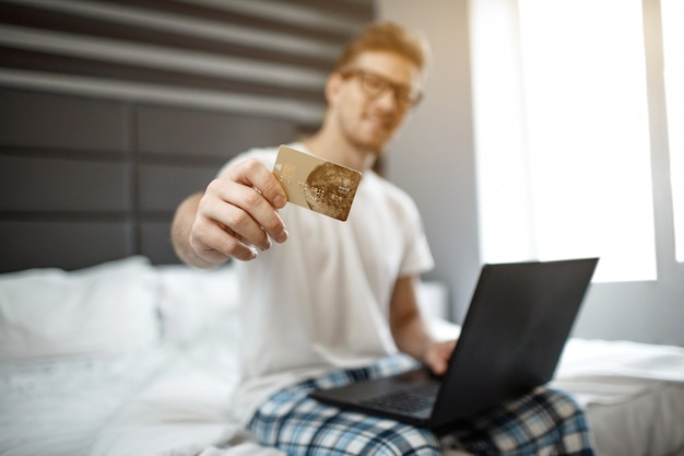 Nice young man sit on bed early morning. he show credit card on camera. guy hold laptop. electronic money.