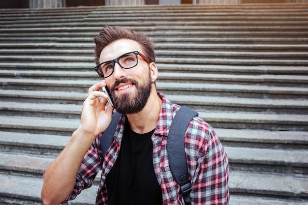 좋은 젊은이 계단에 앉아서 올려. 그는 전화로 이야기합니다. 남자는 안경을 쓴다. 그는 기다리고있다. 젊은 남자는 행복합니다.