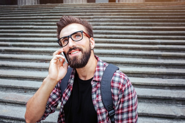 Nice young man sit on stairs and look up. he talks on phone. guy wears glasses. he is waiting. young man is happy.