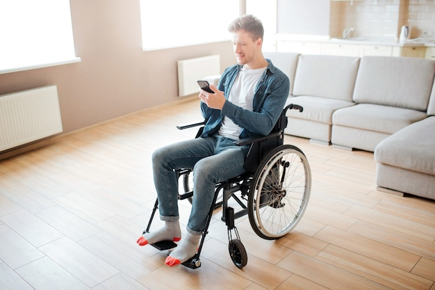 Nice young man with inclusion and disability. sitting on wheelchair. holding phone in hands and look at it. daylight in big empty room.