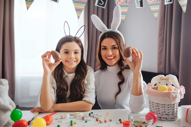 Nice young mother and daughter prepare for easter in room. they hold colorful eggs and pose on camera. people smile. decoration with basket and paint on table.