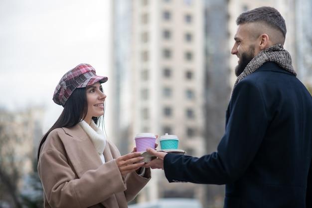 Симпатичные молодые люди смотрят друг на друга за чашками с кофе