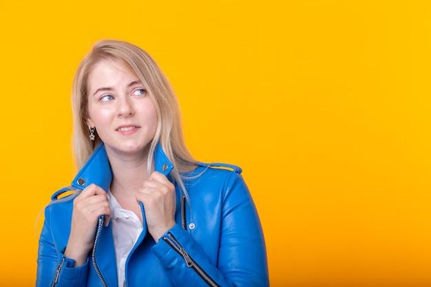 Милая молодая позитивная девушка блондинка в синей кожаной куртке позирует на желтом фоне с копией пространства