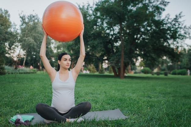 좋은 젊은 임신 한 여자는 공원에서 로터스 포즈에 앉아. 그녀는 손으로 큰 오렌지 피트니스 볼을 잡고 오른쪽을 봅니다. 그녀는 운동한다.
