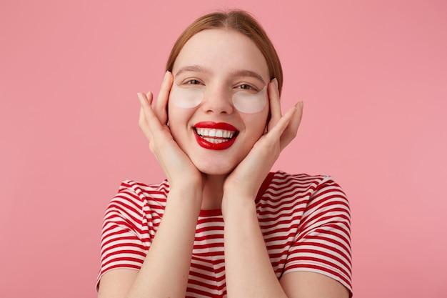 붉은 입술을 가진 빨간 줄무늬 티셔츠를 입은 멋진 젊은 빨간 머리 아가씨는 손가락으로 얼굴을 만지며 눈 아래 다크 서클의 새로운 패치에 매우 만족합니다. 스탠드.