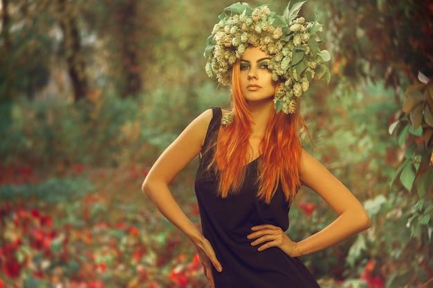 森の中で屋外でポーズをとって頭にホップを持つ素敵な若い赤毛の女性
