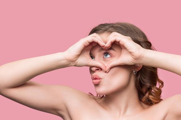 長いウェーブのかかった絹のような髪を持つ素敵な若い笑顔の女性、ピンクの壁に隔離されたあごの近くの手で自然なメイク。