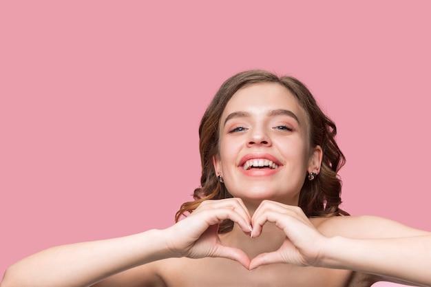 긴 물결 모양의 부드러운 머리를 가진 좋은 젊은 웃는 여자, 분홍색 벽에 고립 된 턱 근처 손으로 자연 메이크업.