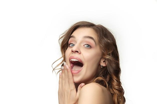 긴 물결 모양의 부드러운 머리를 가진 좋은 젊은 웃는 여자, 흰 벽에 고립 된 턱 근처 손으로 자연 메이크업. 산뜻하고 윤기 나는 피부와 자연스러운 메이크업으로 모델. 사람들의 감정