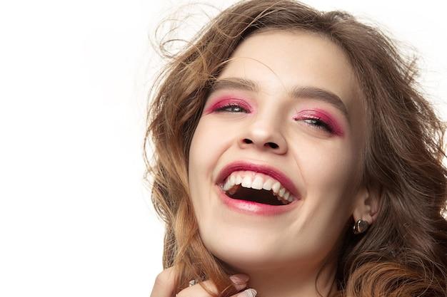 長いウェーブのかかった絹のような髪、白で隔離されたあごの近くの手で自然なメイクアップの素敵な若い笑顔の女性