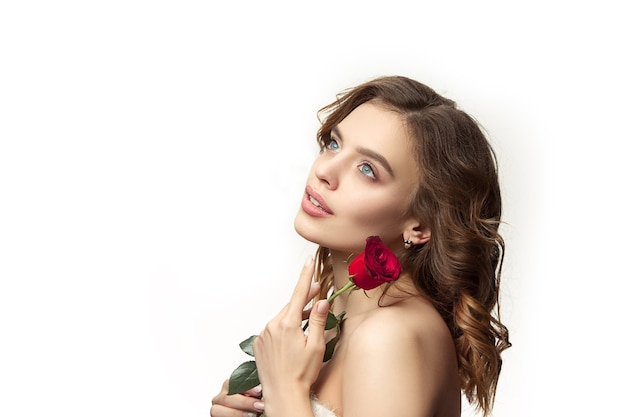 長い波状の絹のような髪、白い壁に分離された赤いバラで自然なメイクアップの素敵な若い笑顔の女性。みずみずしいツヤ肌とナチュラルメイクのモデル。人々の感情