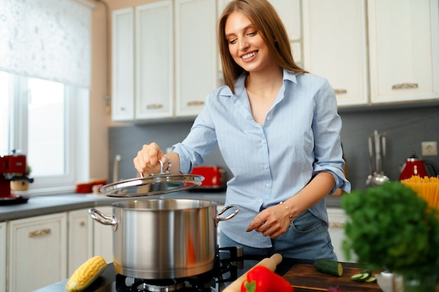 彼女の台所のストーブのそばで鍋で何かを調理する素敵な若い女性