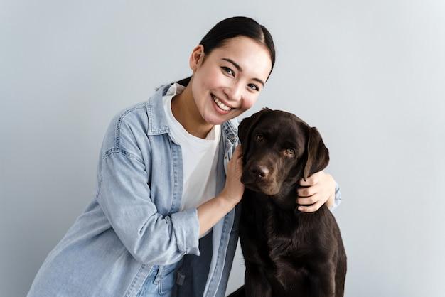 그녀의 애완 동물과 회색 배경에 고립 된 좋은 젊은 여자