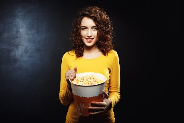 Nice young woman playing with popcorn looking straight