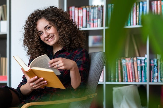 Nice young woman sits  in the chair and  leafing through the book smiling playfully