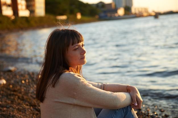Милая молодая женщина, сидящая на пляже на закате