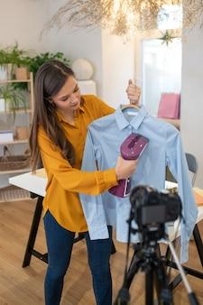 シャツにアイロンをかける方法を示している間、カメラの前に立っている素敵な若い女性