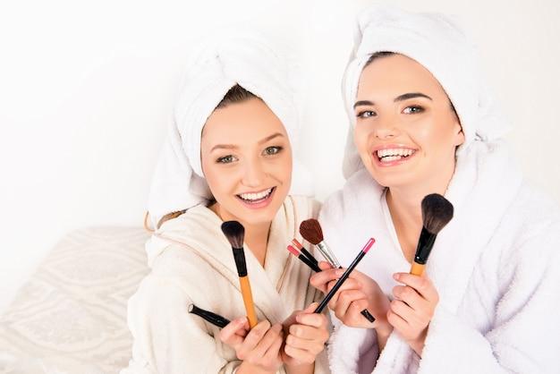 頭にタオルで化粧ブラシを持っている素敵な若い女性