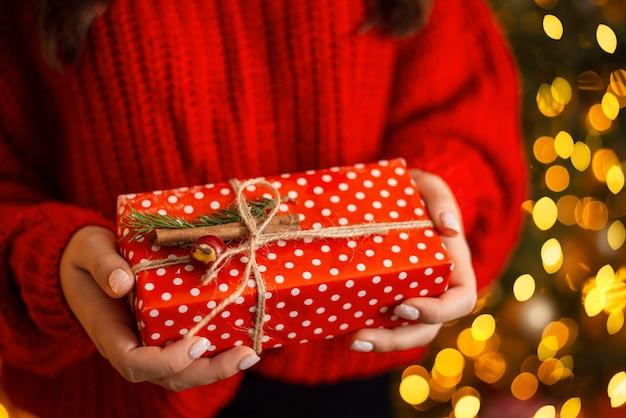 Красиво оформленная подарочная коробка в красной оберточной бумаге в руках молодой женщины