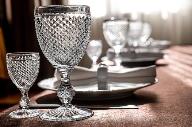 素敵なレストランのテーブル。グラス、ワイングラス、カトラリー、お皿、ナプキンを備えたテーブルセッティング。