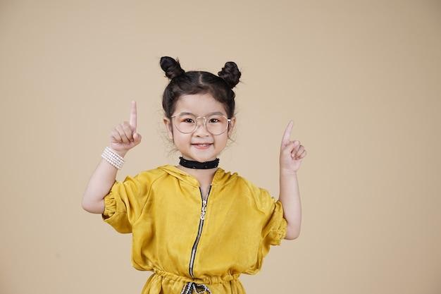 フリーテキストスペースでベージュの背景に黄色のドレスアップで素敵な笑顔のアジアのファッションの子供の女の子