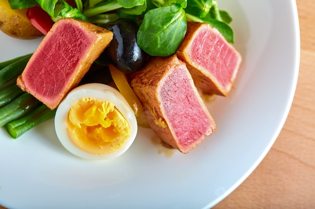Nicoise salad with grilled tuna and boiled egg on a wooden background
