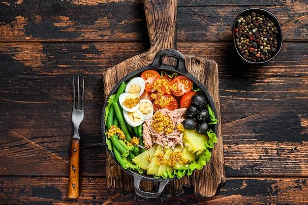 マグロ、チェリートマト、オリーブ、インゲン、きゅうり、半熟卵、ジャガイモのニコイズサラダ。暗い木の背景。上面図。