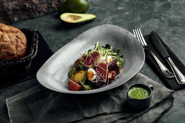 Салат нисуаз с тунцом на серой тарелке, на сервировочном столе. красивое блюдо от шеф-повара, фото еды, серый фон, копировальное пространство, традиционная французская кухня.