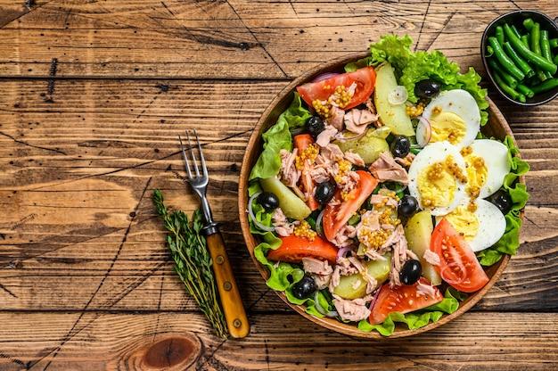 マグロ、トマト、オリーブ、インゲン、きゅうり、ゆで卵、ジャガイモを木製のボウルに入れたニコイズサラダ。木製の背景。上面図。スペースをコピーします。