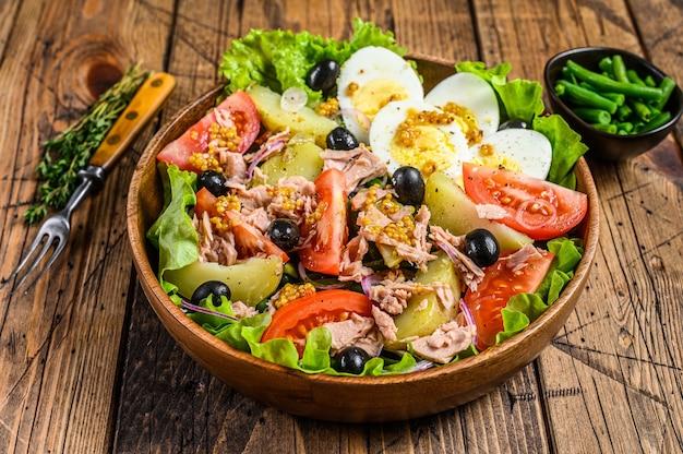 マグロ、トマト、オリーブ、インゲン、きゅうり、ゆで卵、ジャガイモを木製のボウルに入れたニコイズサラダ。木製のテーブル。上面図。