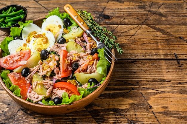 マグロ、トマト、オリーブ、インゲン、きゅうり、半熟卵、ジャガイモの木製ボウルにニコイズサラダ