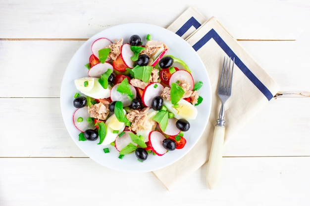 Салат nicoise с тунцом, яйцом, помидорами черри и маслинами. французская кухня. вид сверху