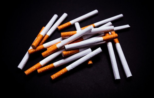 Никотиновая зависимость, много сигарет на черном изолированном фоне