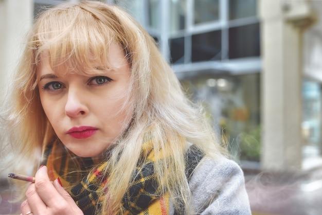 ニコチン中毒非常に機嫌が悪い女性。手に持って、指の間でくすぶっているタバコを吸っている。タバコのクローズアップ。