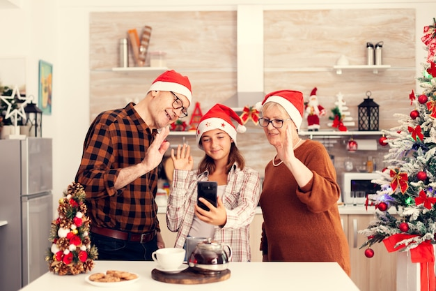 Племянница, бабушка и дедушка празднуют рождество и здороваются