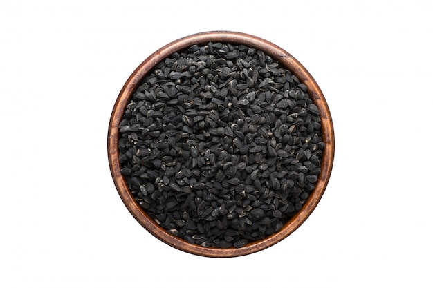 白い背景に分離された木製のボウルにニゲラやブラッククミンの種子のスパイス。調味料のトップビュー