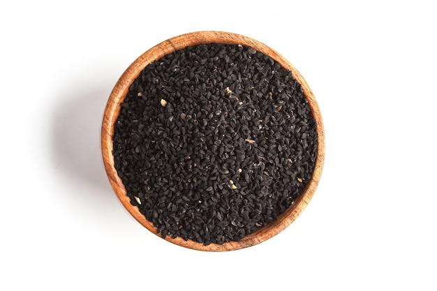 Nigella sativa or black cumin in wooden bowl on white background, copy space, top view, isolate