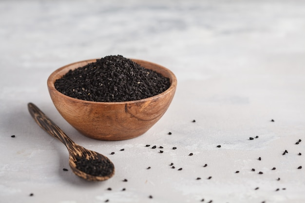Nigella sativa or black cumin in wooden bowl on white background, copy space