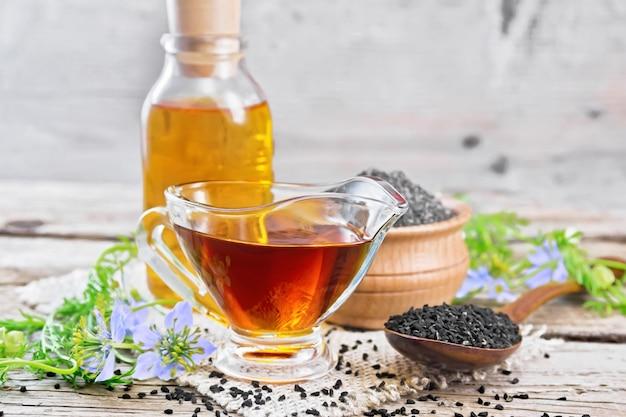 소스보트와 병에 든 나이젤라 사티바 오일, 숟가락에 든 씨앗, 삼베 위에 있는 그릇에 든 블랙 커민 가루, 오래된 나무 판자 배경에 파란 꽃과 녹색 잎이 있는 칼링이 잔가지