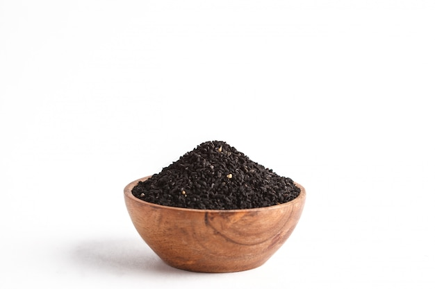 Nigella sativaまたは黒クミンの白い背景の上、木製のボウルにコピースペース、分離します。
