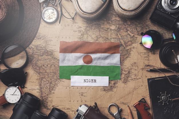 Флаг нигера между аксессуарами путешественника на старой винтажной карте. верхний выстрел